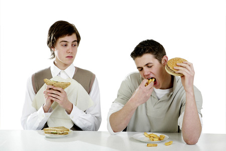 Man looking at his friend eating greedily