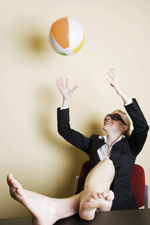 Businesswoman playing with beach ball in the office photo