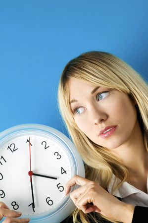 ticking away: Businesswoman holding a clock Stock Photo