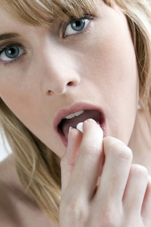 Woman eating pill Stock Photo - 26231677
