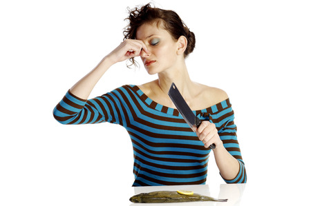 Woman closing her nose while cutting a fish photo