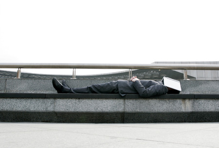 closed business: Businessman sleeping on the bench with a book covering his face Stock Photo