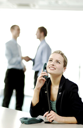 Businesswoman on the phone while businessmen shaking hands on the background photo