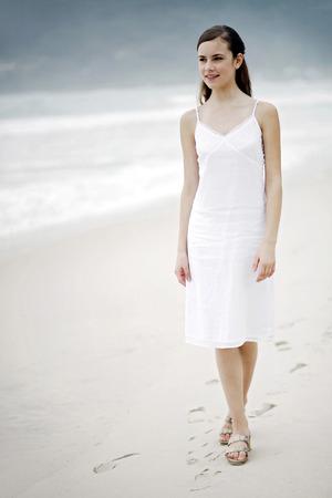 stroll: Woman taking a stroll along the beach Stock Photo