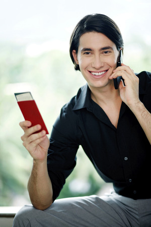Man holding passport while talking on the mobile phone photo