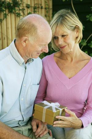 Senior lady holding a gift sitting beside her husband photo