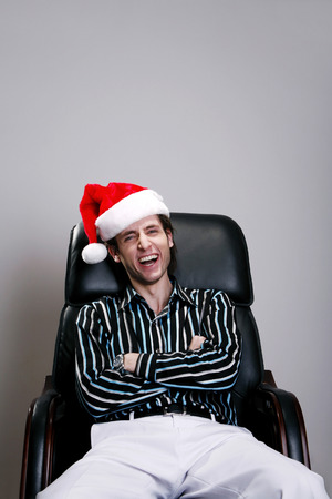 Businessman with christmas hat sitting on the chair laughing photo