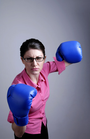 Businesswoman with blue boxing gloves photo