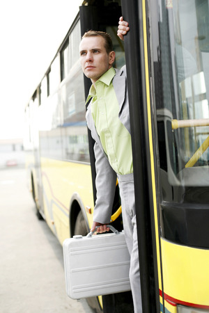 he is public: Businessman getting down from a bus
