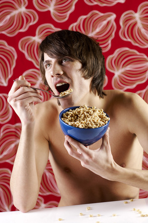 bare waist: Man having breakfast cereal