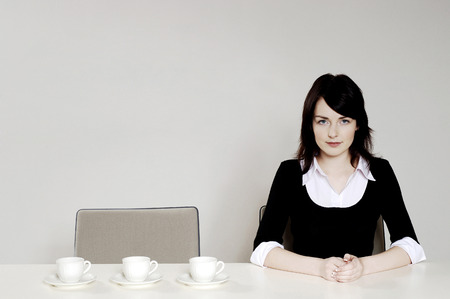 Businesswoman with three coffee cups beside her photo