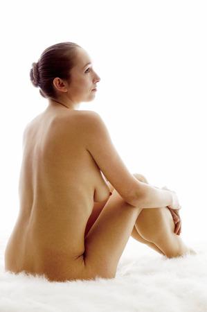 junge frau nackt: Nackte junge Frau sitzt auf wei�em Fell Lizenzfreie Bilder