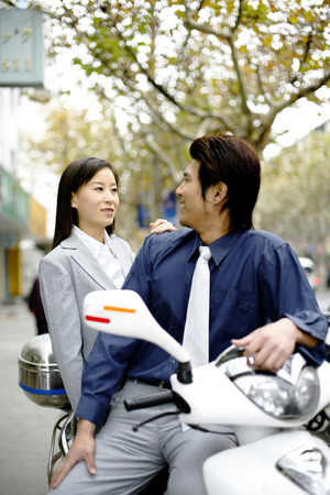 Businessman and businesswoman sitting on the scooter talking photo