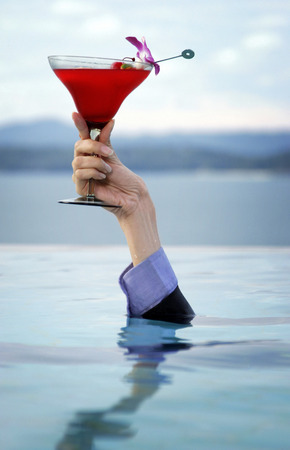 Hand coming out from the water holding a glass of cocktail photo