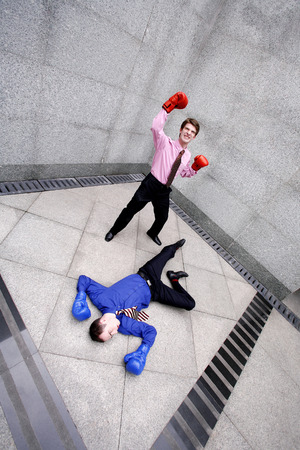 fainted: Businessman with boxing gloves celebrating after defeating his opponent