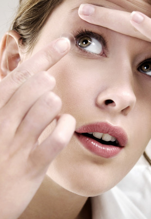Woman putting on contact lens Stock Photo - 26202516