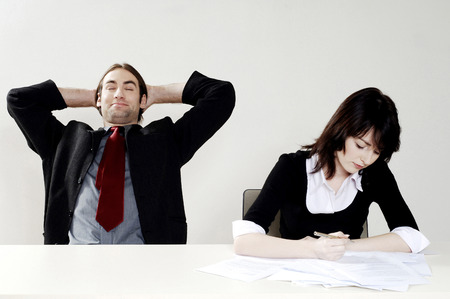 Businessman relaxing while his colleague is doing her work photo