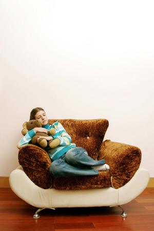 Teenage girl hugging her teddy bear while sleeping photo