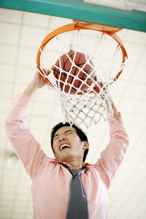 Businessman dunking basketball Stock Photo