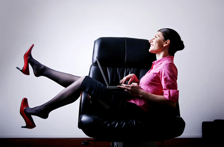 Businesswoman smiling while using laptop photo