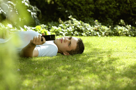 Teenage boy lying on the field taking his own picture with camera phone photo