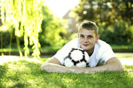 lying forward: Teenage boy lying forward on the field hugging a soccer ball Stock Photo