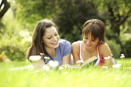 revision book: Teenage girls lying forward on the field reading book