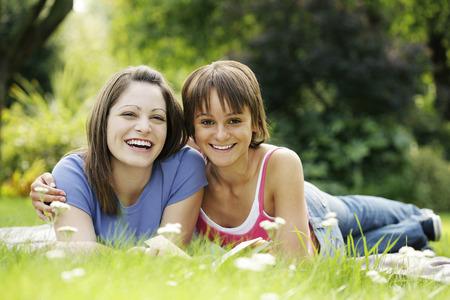 lying forward: Teenage girls lying forward on the field sharing a book Stock Photo