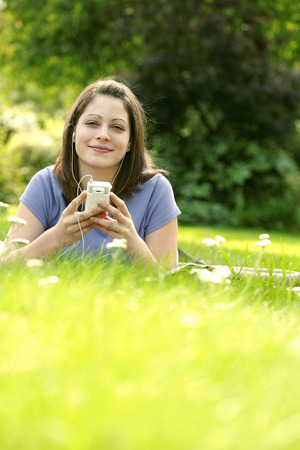 lying forward: Teenage girl lying forward on the field listening to music on a portable MP3 player