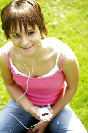 Teenage girl sitting on the field listening to music on a portable MP3 player photo