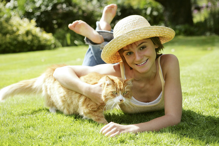 lying forward: Teenage girl lying forward on the field with her cat