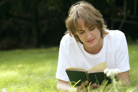 revision book: Teenage boy lying forward on the field reading book