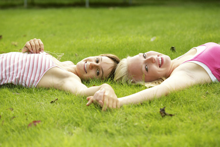 Teenage girls holding hands while lying on the field photo