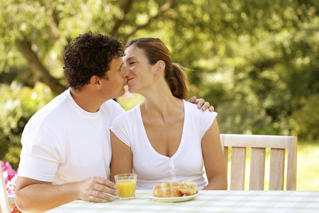 Couple sitting at the picnic table kissing photo
