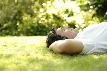 Man listening to music on the headphones while lying on the field photo