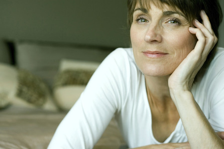 lying forward: Woman lying forward on the bed smiling at the camera Stock Photo