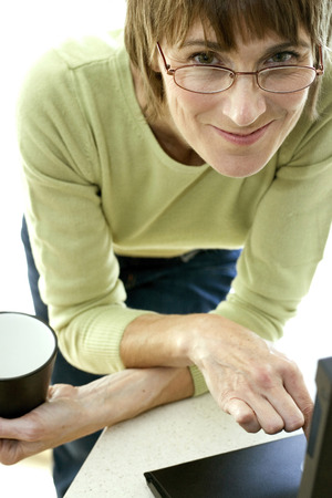 Woman holding a cup of coffee while using laptop photo