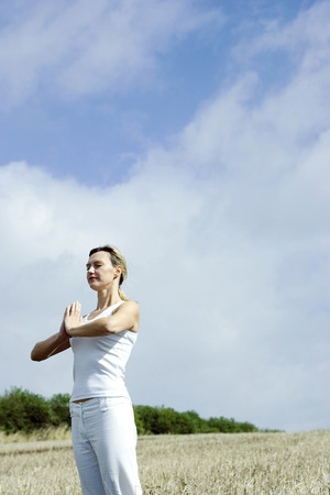 Woman practicing yoga on the field photo