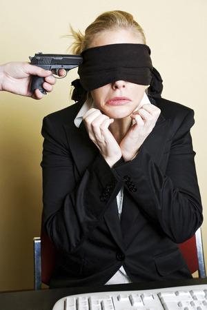 Arma que se apunta a una mujer de negocios con los ojos vendados