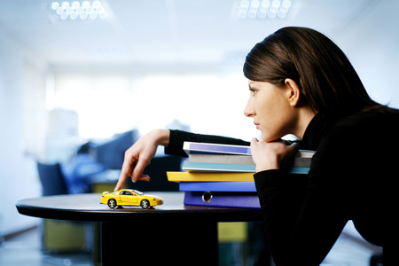 Businesswoman playing with toy car while thinking photo