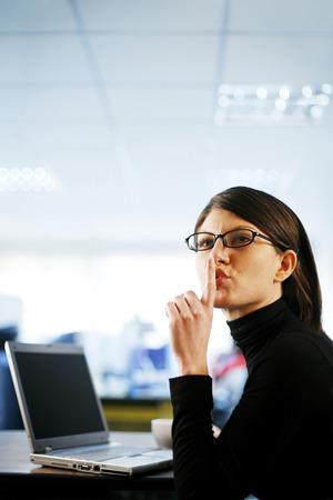hushing: Businesswoman showing hushing sign