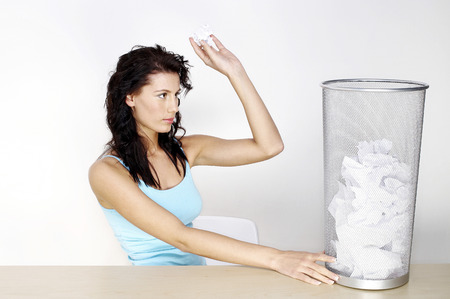 Woman throwing crumpled paper into the dustbin photo