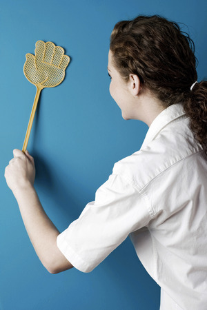 Woman using a fly swatter Stock Photo - 26229335