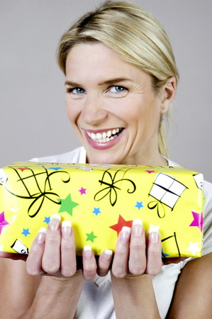Woman smiling while holding a present photo