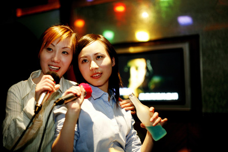 after to work: Empresarias karaoke cantando despu�s del trabajo Foto de archivo