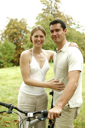 Couple with their bicycle in the park photo