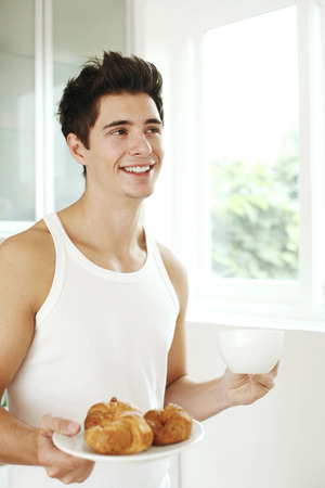 Man with a cup of coffee and a plate of croissants photo