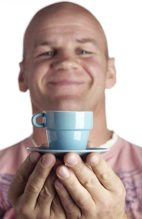 Man holding a small cup and saucer photo