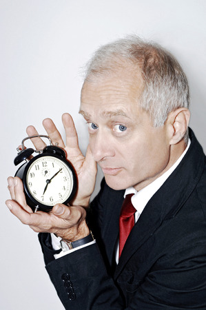 Businessman holding an alarm clock photo