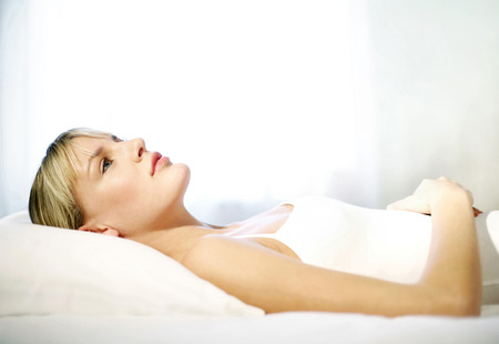 Woman lying on the bed thinking photo
